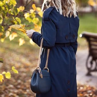 スタイリッシュな女性は、秋の公園を散歩します。