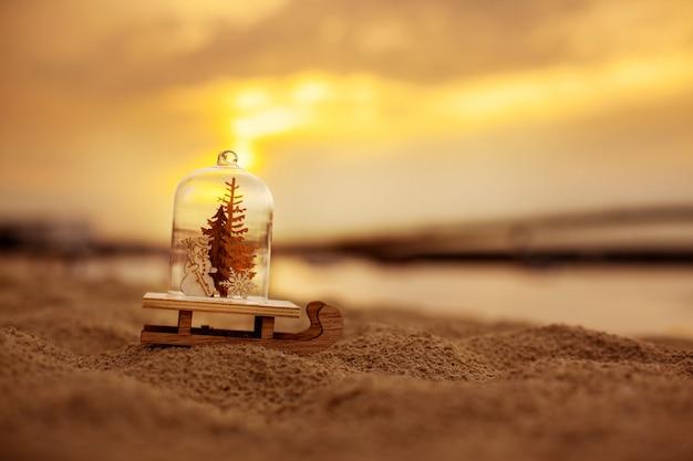 Новогоднее украшение в виде стеклянного шарика с елкой и снеговиком на пляже