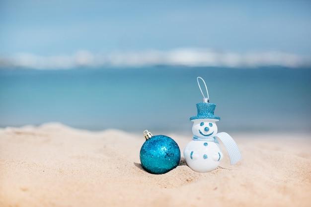 Снеговик в синей шляпе и синий новогодний шар