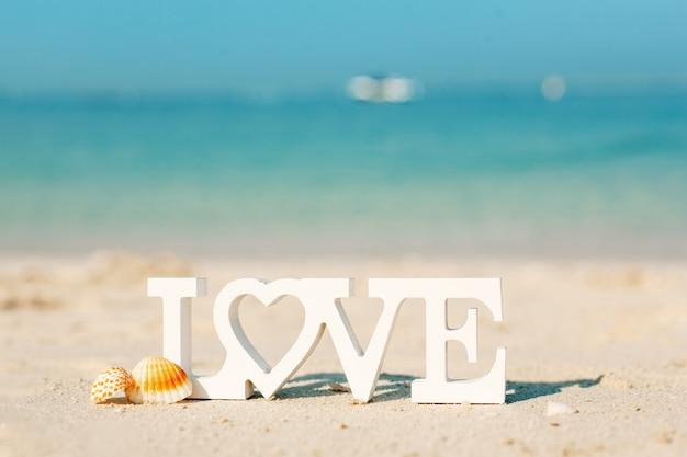 Деревянные буквы любят на песчаном пляже с видом на синее море