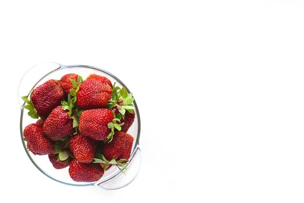 テキスト用のスペースと白い背景で隔離のボウルにジューシーな熟したイチゴ