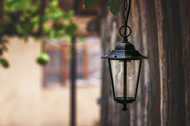Черное стекло старинный уличный фонарь висит во дворе