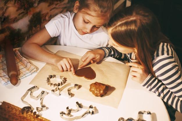 テーブルで家庭の台所で美しい女の子が生地からハート型のクッキーを切り取る