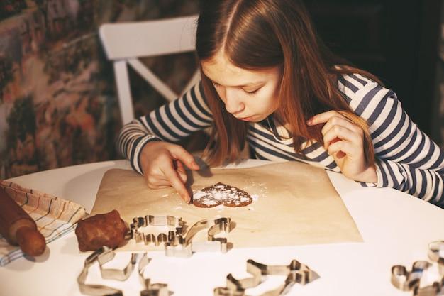 テーブルで家庭の台所で魅力的な笑顔の女の子は、生地からハート型のクッキーを切り取りました