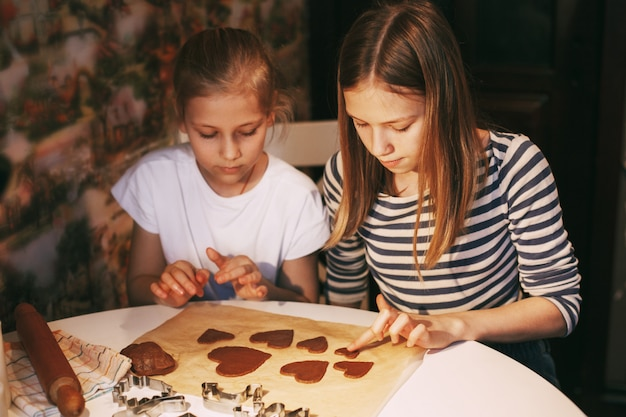 Красивые девушки на домашней кухне за столом вырезали из теста печенье в форме сердца