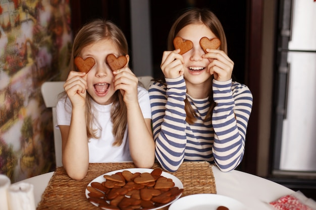 面白くて笑っている女の子はハート型のクッキーを持ち、目を閉じてばかにする
