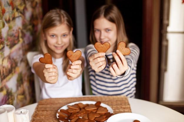 ぼやけた背景の陽気な笑っている姉妹は伸ばした腕にハート型のクッキーを保持します