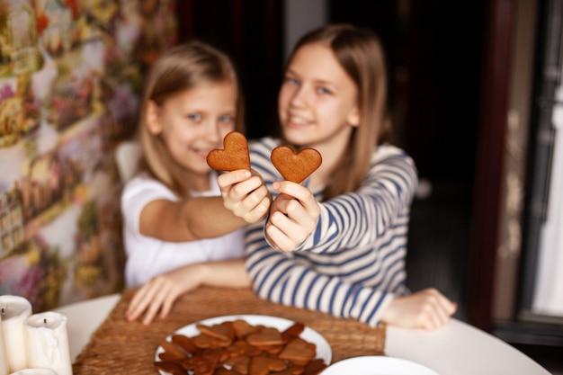 陽気で笑っている姉妹は、伸ばした腕にハート型のクッキーを持っています