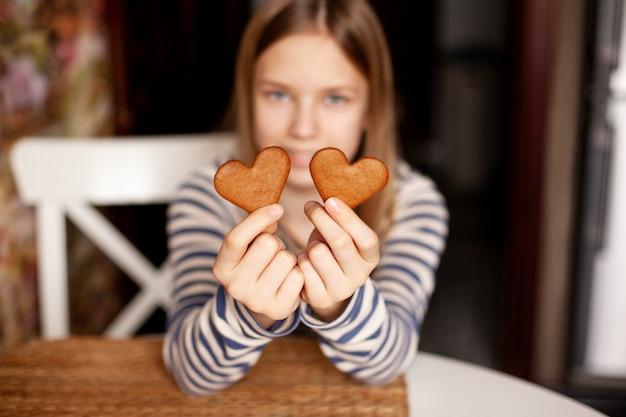 ぼやけた背景に微笑んでいる女の子が伸ばした腕にハート型のクッキーを保持