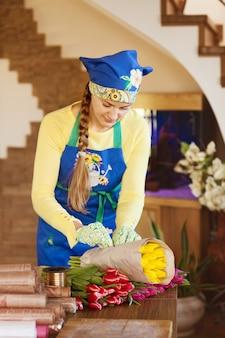 Девушка-флорист упаковывает красивые тюльпаны в цветочный магазин в крафт-бумаге