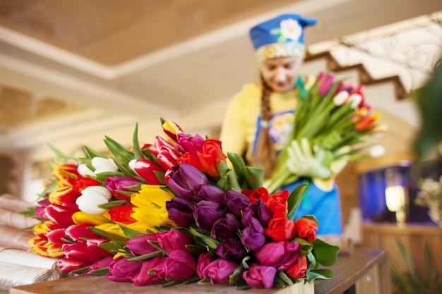 女の子の花屋はクラフトペーパーのフラワーショップで美しいチューリップを梱包します。