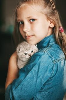 Девочка обнимает британского маленького котенка