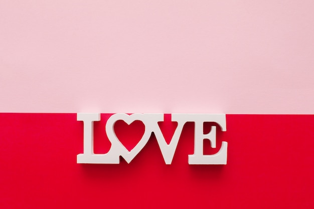 Слово любовь состоит из деревянных букв, расположенных на розовом и красном фоне, вид сверху
