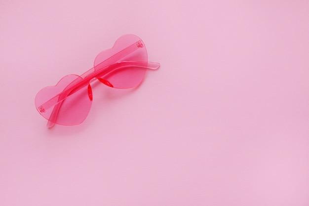 ピンクのハート型のピンクの背景にメガネ