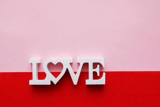 愛という言葉は、ピンクと赤の背景にある木製の文字で構成されています
