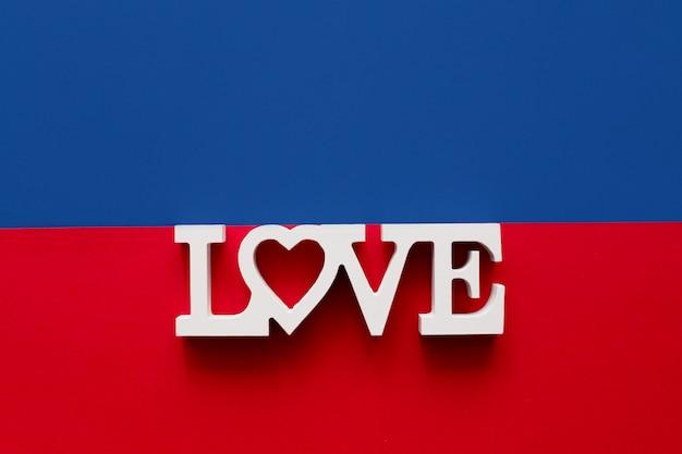 明るい青と赤の背景にある木製の白い文字で作られた愛という言葉