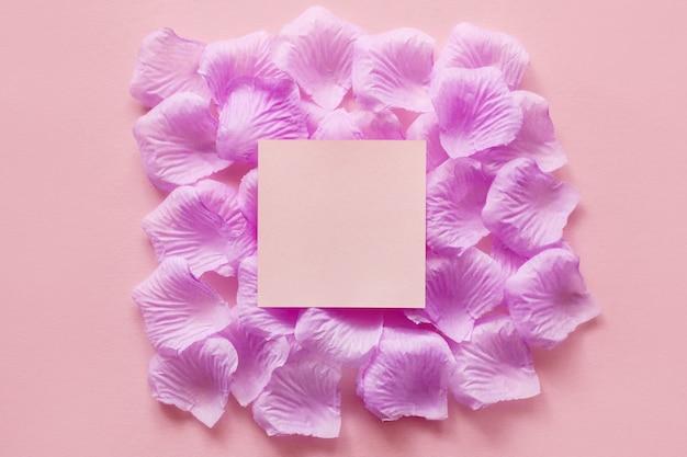 Красивый розовый фон с лепестками цветов и квадратным пространством в центре для добавления текста