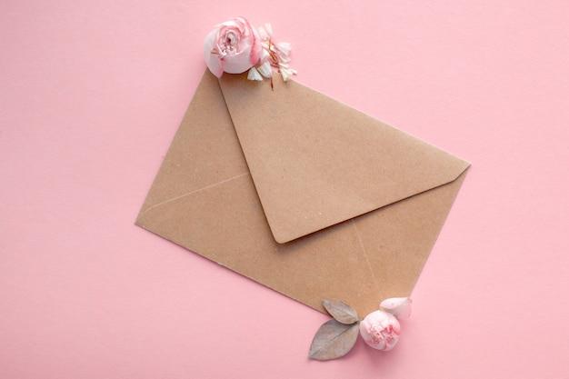 淡いピンクの背景にクラフト紙から封筒にピンクのバラ