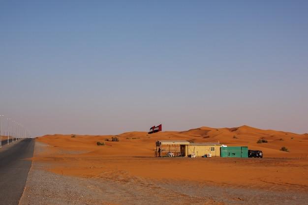 砂丘を通って曲がりくねった黒いアスファルト道路