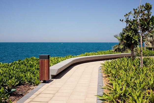 ドバイの青い水島の海沿いの道を歩く