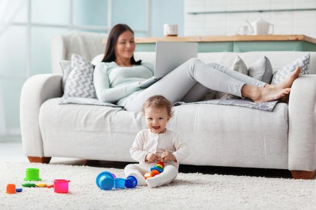 Мама работает за ноутбуком дома, пока ее ребенок играет с игрушками на полу