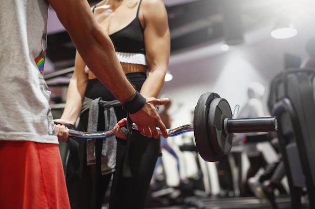 パーソナルトレーナーは、ジムでのトレーニング中に若い女性にバーベルを使ったエクササイズの正しい実装を示します