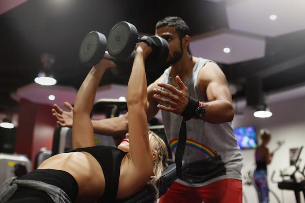 パーソナルトレーナーは、ジムでのトレーニング中にダンベルでのエクササイズの正しい実装を若い女性に示します