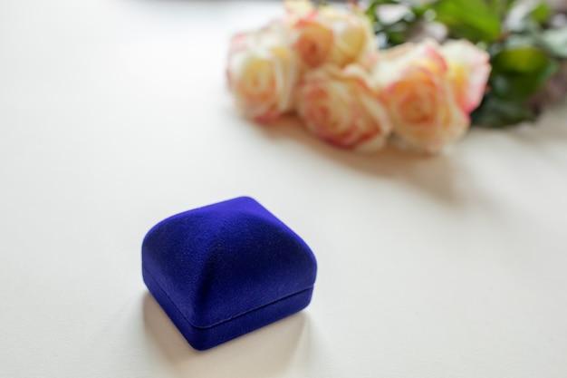 Подарочная коробка с украшениями и розами на столе