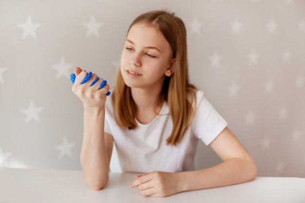 Молодая девушка сжимает голубую слизь рукой и смотрит на нее с улыбкой