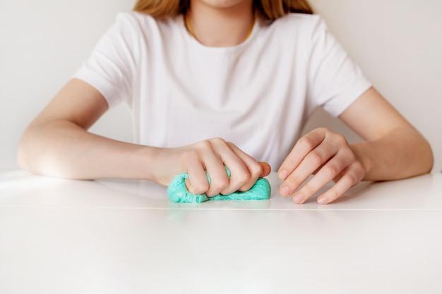 Девушка сжимает голубую слизь рукой
