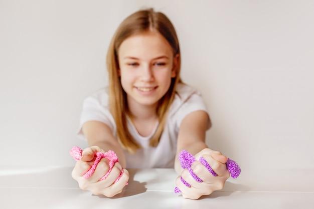 Молодая девушка сжимает розово-фиолетовую слизь в руках и смотрит на нее с улыбкой