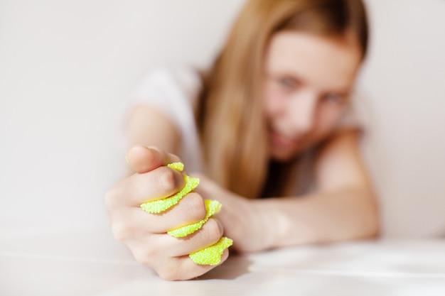 Молодая девушка сжимает желтую слизь рукой и смотрит на нее с улыбкой