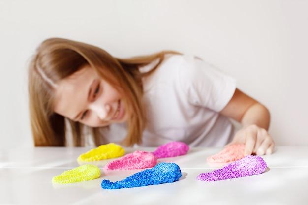 Красивая девушка улыбается и смотрит на разноцветную слизь, лежащую на столе