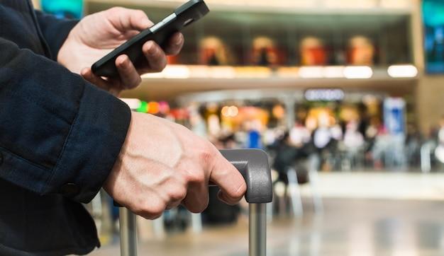 男の手を保持しているスーツケースのハンドルを閉じる