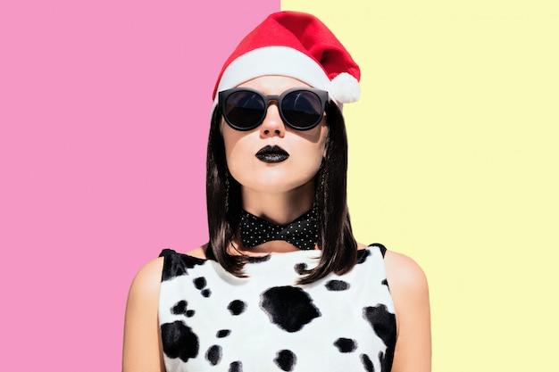 Портрет красивой женщины в рождественском наряде и солнцезащитные очки с черными краской губами на фоне красочных