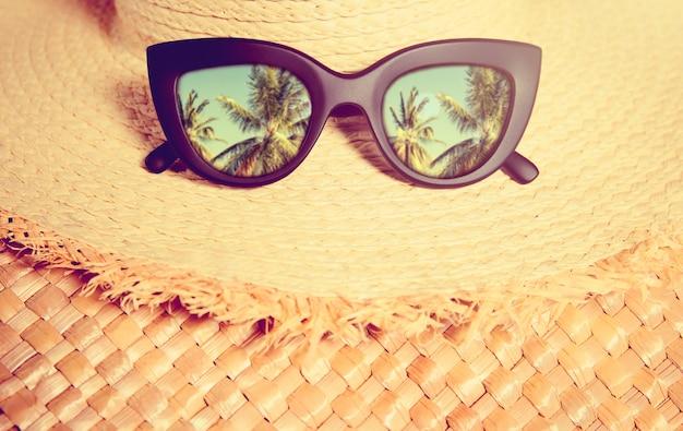 Соломенная шляпа с черными модными очками с отражением в них ладоней на соломенной сумке.
