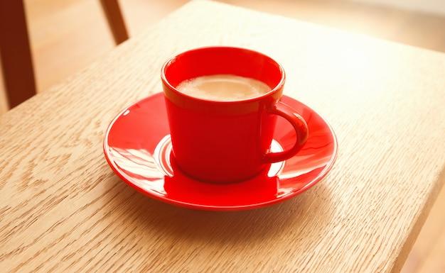 木製のテーブルの上のコーヒーの赤カップ