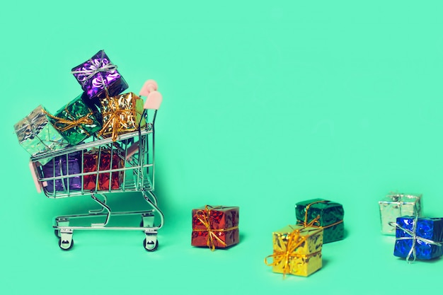 カラフルなプレゼントボックスと小さな装飾トロリー。販売およびショッピングのコンセプト。