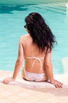 Девушка загорает в бассейне