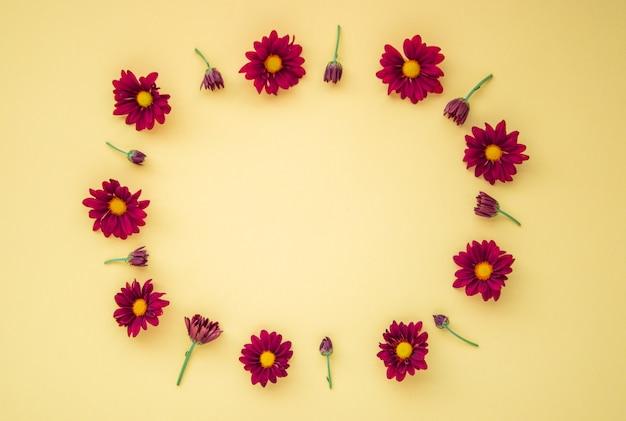 花の組成物。黄色の背景にさまざまな赤い花で作られた花輪