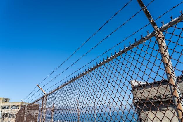 Металлический забор с колючей проволокой на запретной территории