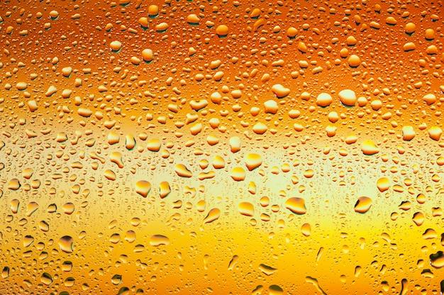 抽象的なテクスチャオレンジ色の背景を持つガラスに水滴