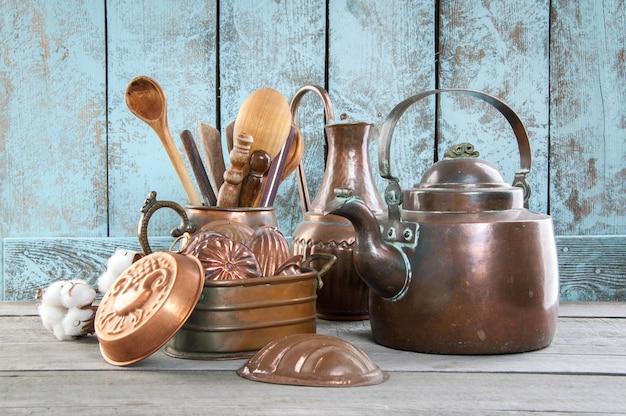 木製の青色の背景にヴィンテージの銅食器。