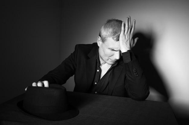 Мужчина средних лет с черной шляпой