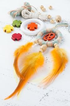 オレンジ色のピースサインと明るいドリームキャッチャー