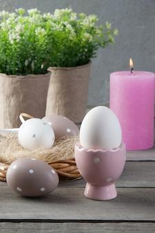 卵と古い木製の背景にバラのアロマキャンドル