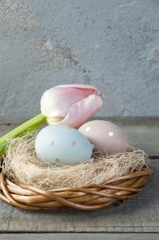 卵と古い木製の背景にチューリップ