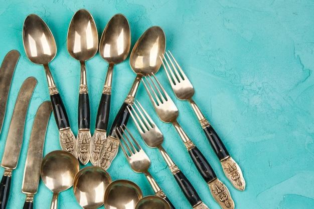 真鍮のスプーン、フォーク、ナイフ、コンクリートの背景に。