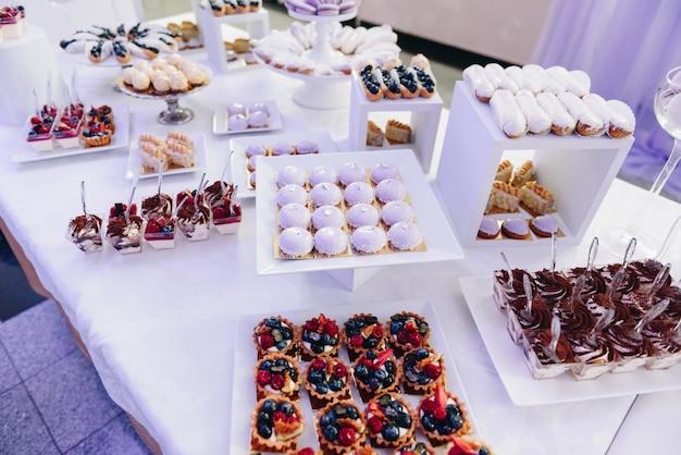 おいしいデザート、ケーキ、カップケーキ、ペストリーのおいしいセレクションを宴会のビュッフェテーブルで