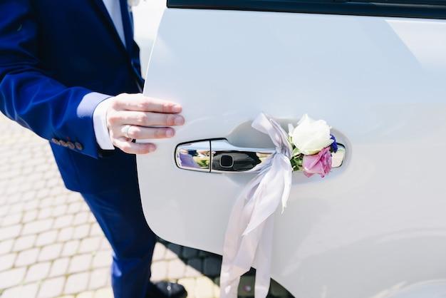 結婚式の車のドアを開ける新郎
